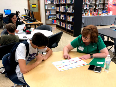 A SECU volunteer works with a high schooler at a Financial Fair, where they learn how to balance a budget in the real world.